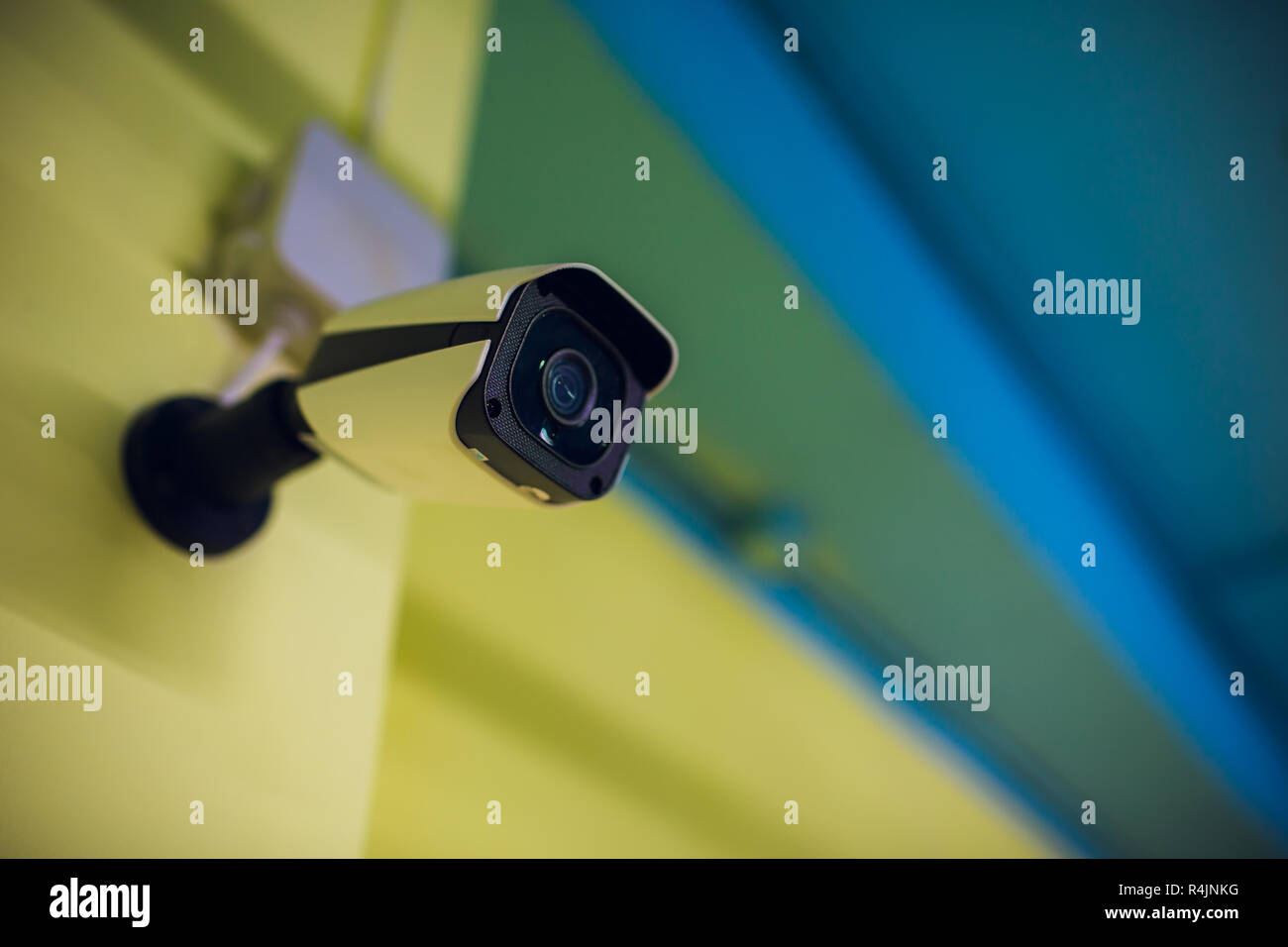 Modern CCTV camera on a wall. A blurred night cityscape background. Concept of surveillance and monitoring. Toned image double exposure mock up. - Stock Image