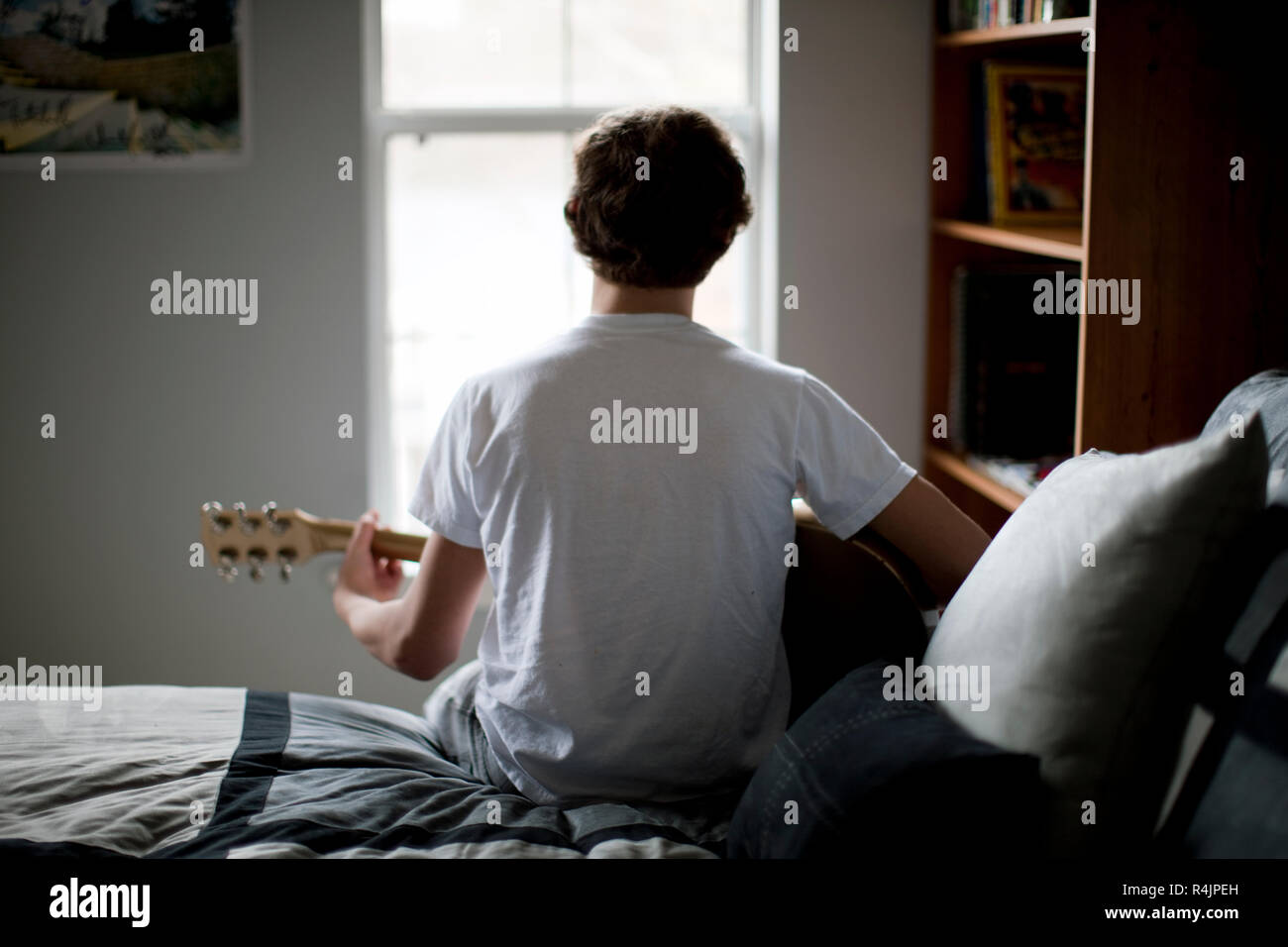 Boy sitting on bed playing guitar. - Stock Image