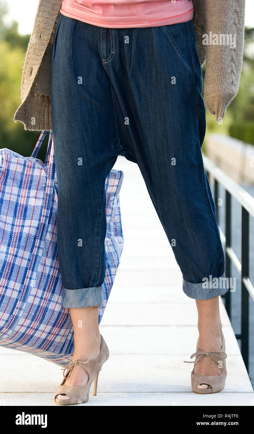 girl wearing 3/4 lengh jeans carrying eco bag with zip - Stock Image