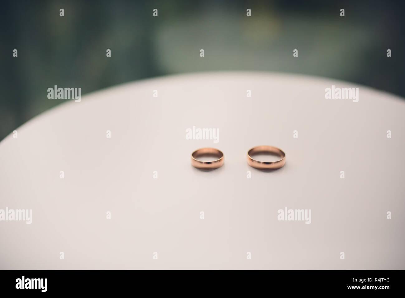 Wedding diamond gold rings engagement rings on white table. - Stock Image