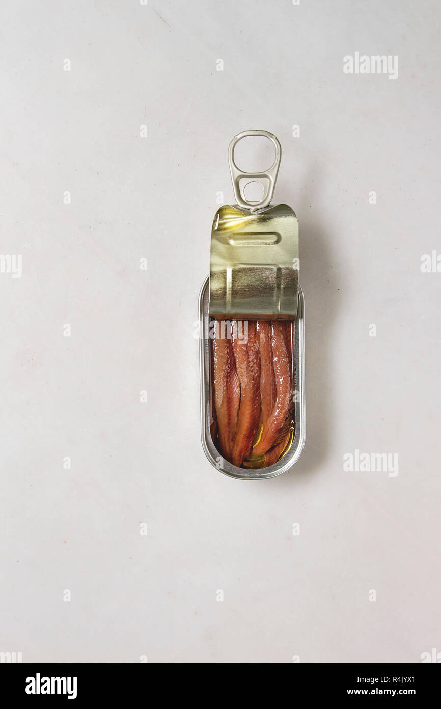 Pickled salted anchovies fillet in oil in open tin can over white marble background. Flat lay, copy space - Stock Image