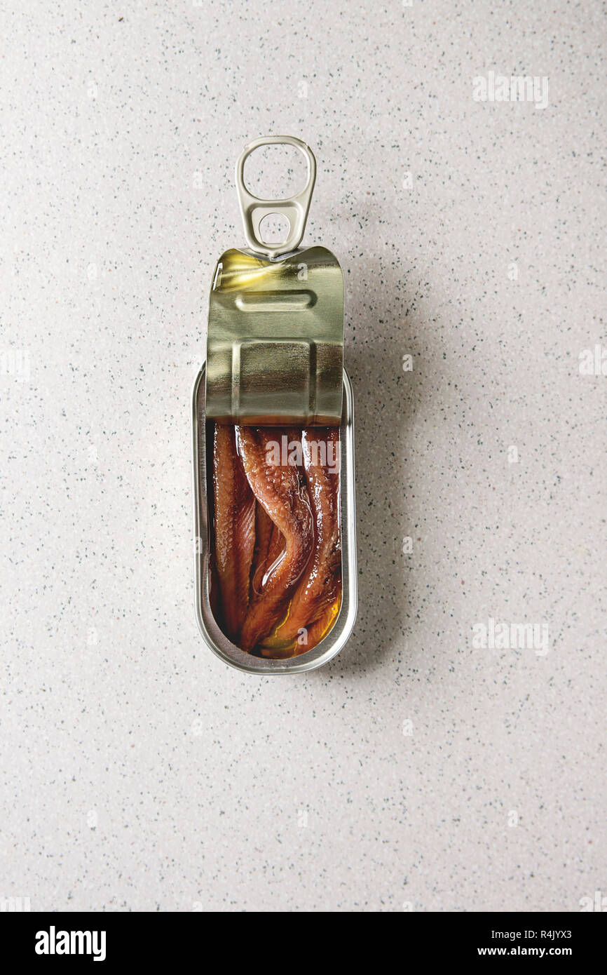 Pickled salted anchovies fillet in oil in open tin can over grey spotted background. Flat lay, copy space - Stock Image
