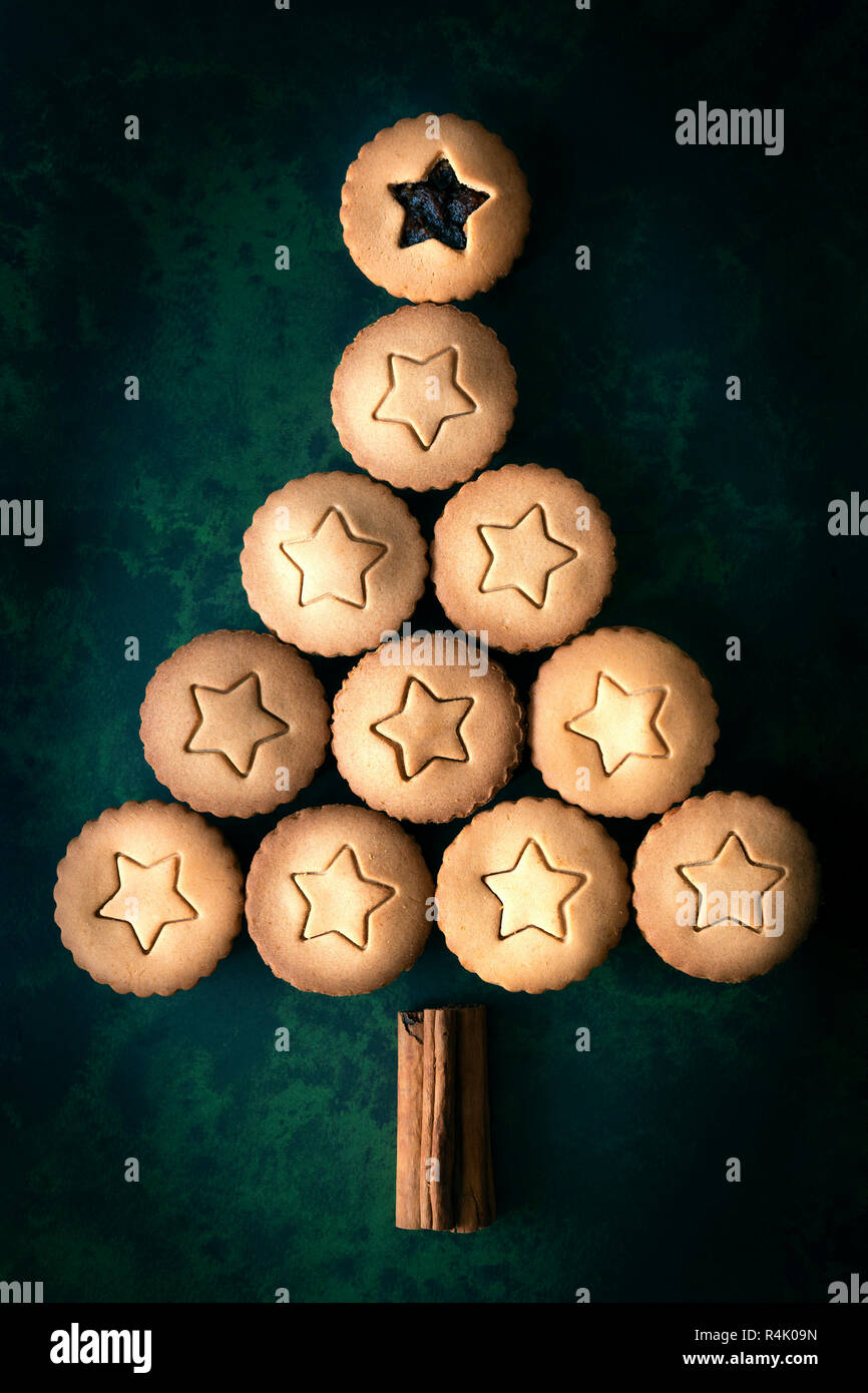A Christmas tree made using gingerbread fruit mince pies and cinnamon sticks. - Stock Image