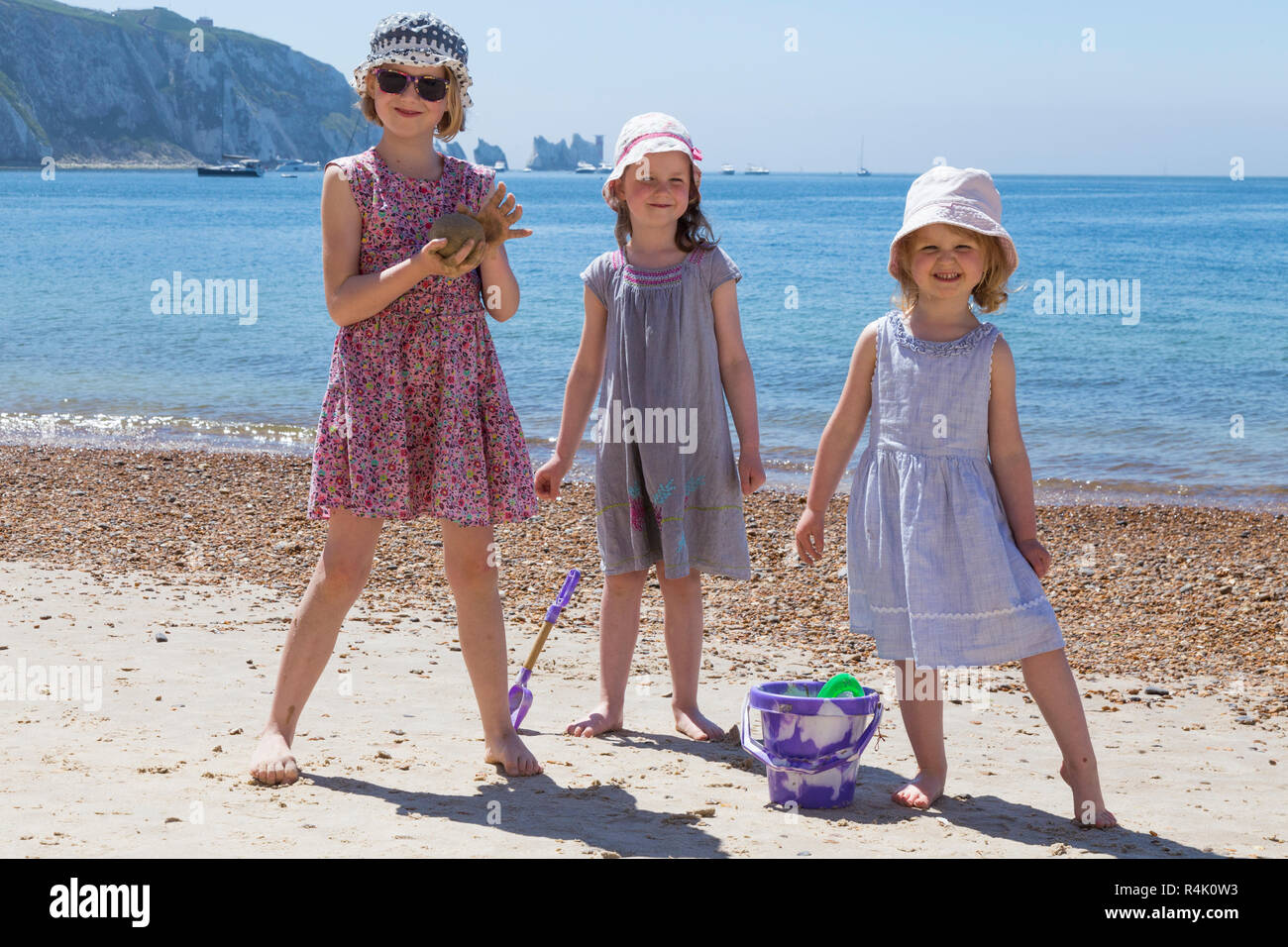 Three sisters, young girls, enjoy a family play on beach at Alum Bay on the Isle of Wight, UK. They wear hats and dresses / clothes to protect from the Sun. (98) - Stock Image