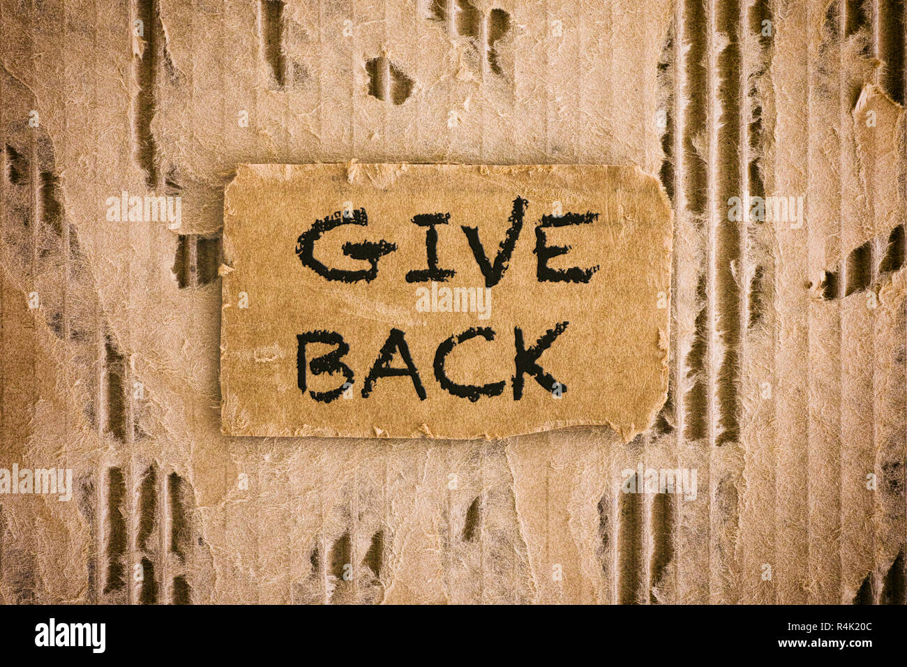 Piece of cardboard with words Give Back on tattered corrugated cardboard background. Close-up. - Stock Image