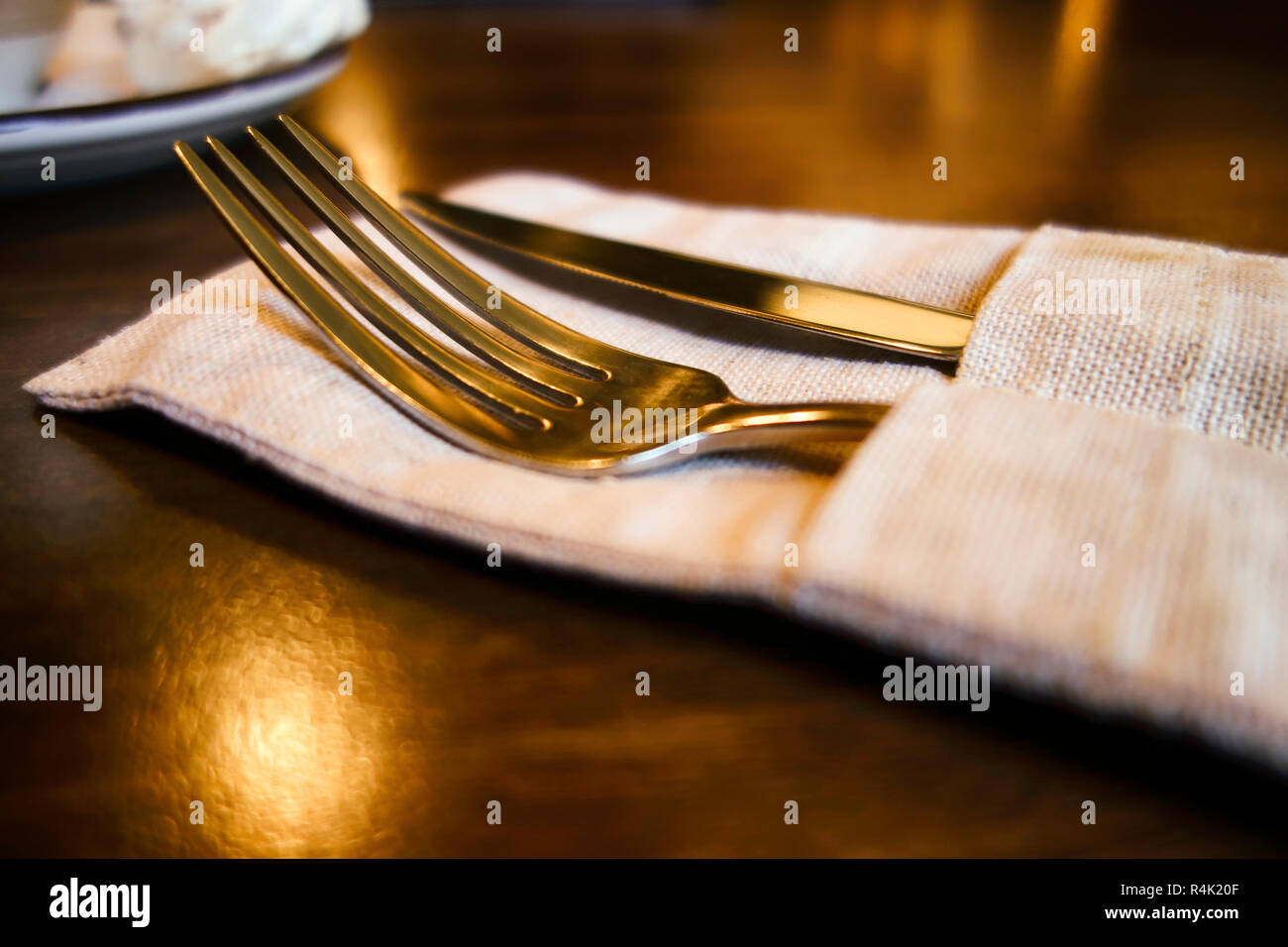 Fork and knife in linen napkin on the table. - Stock Image