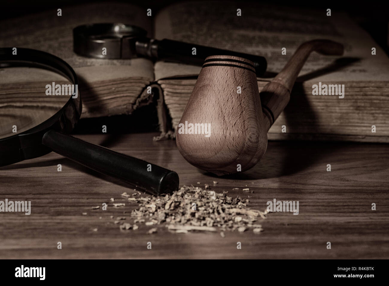 Smoking pipe with tobacco leaves on wooden background. - Stock Image