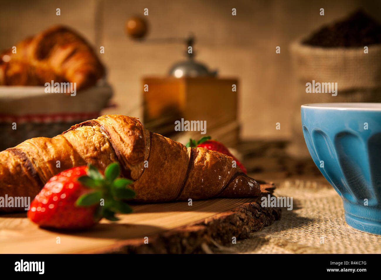 Closeup of a continental breakfast with croissant and a cup of milk - Stock Image