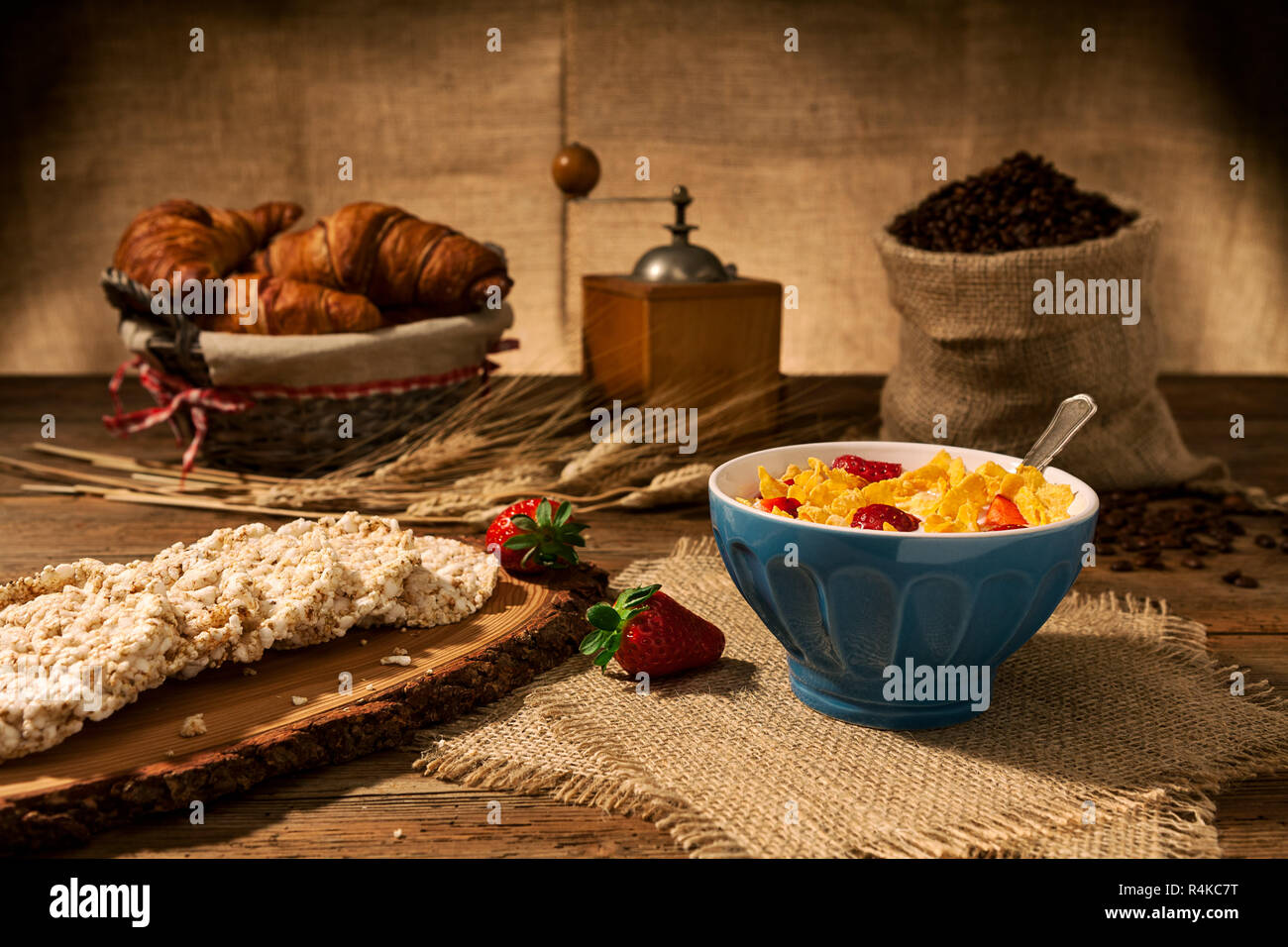 Continental breakfast with cornflakes and strawberries in a cup of milk and rice crackers - Stock Image