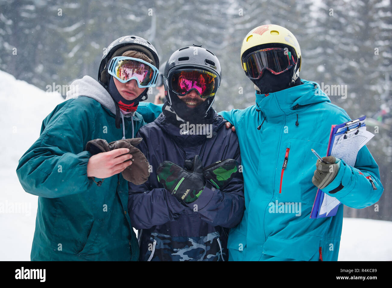 BUKOVEL,UKRAINE-19 MARCH,2018: Winter action sports festival in snow park.Young people compete in big air snowboarding & extreme skiing.Group of athle - Stock Image