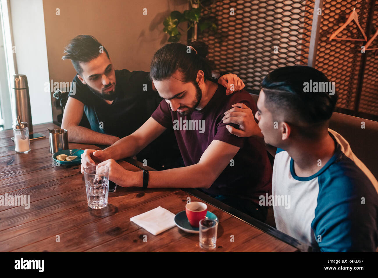 Supportive young men encourage their brokenhearted friend. Arabian guys cheer him up and advise in restaurant. Friendship concept. - Stock Image