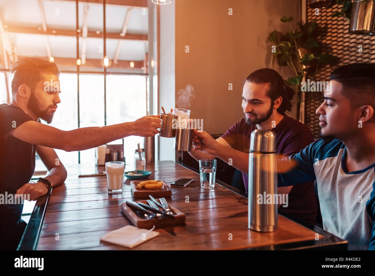 Group of mixed race young men clink glasses in lounge bar. Multiracial friends having fun in cafe drinking tea - Stock Image
