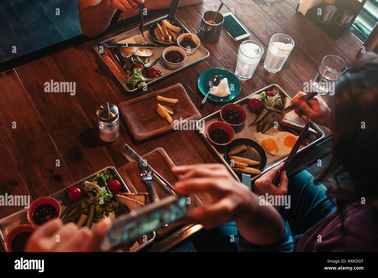 Young man takes a picture of his food on his phone for social network while having breakfast in cafe. Internet addiction concept. - Stock Image