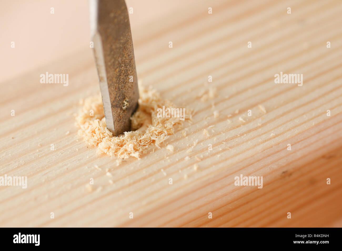 Flat drill bit make hole in wooden bar closeup - Stock Image