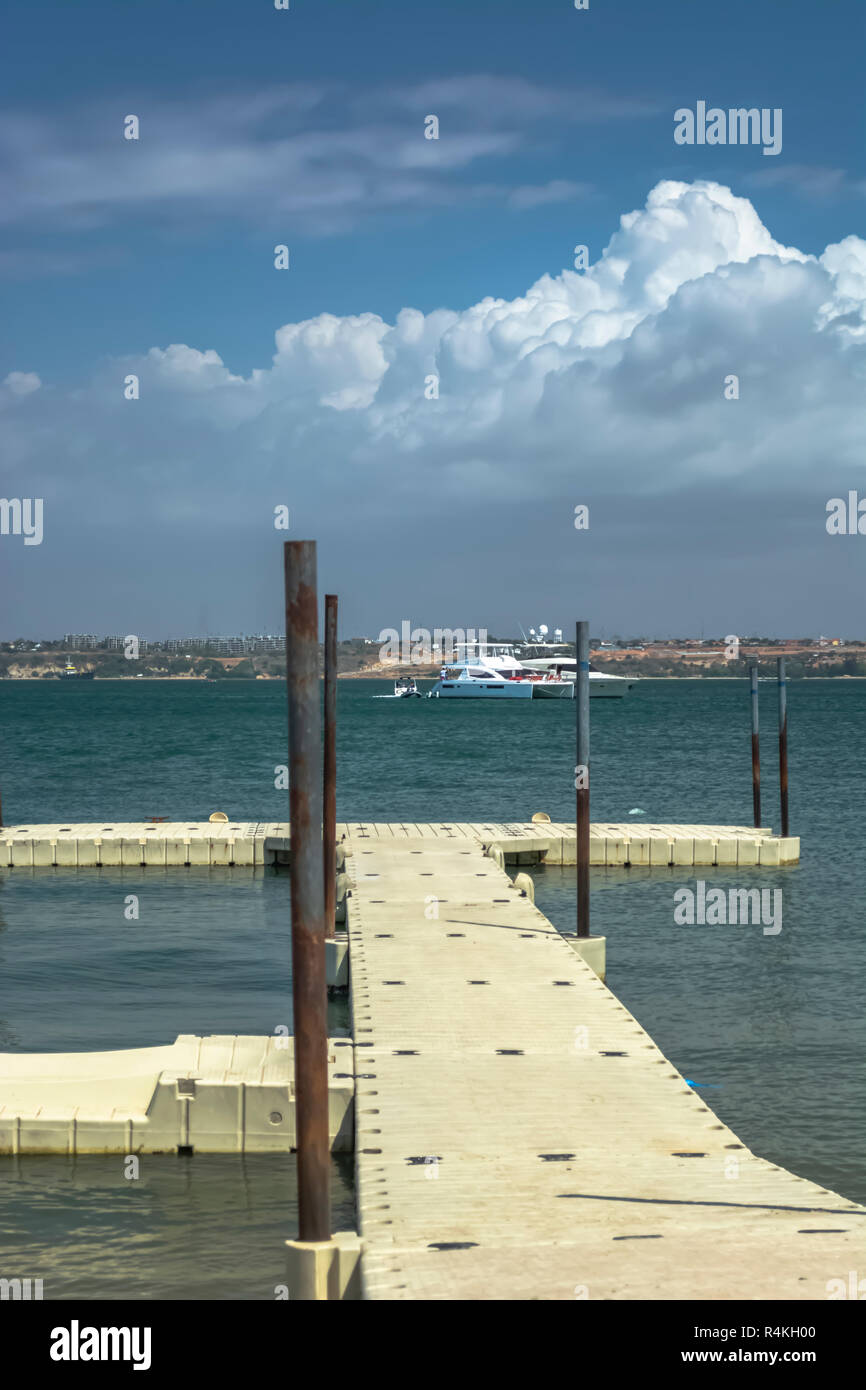 View of small dock, sea and boats, on the coast of Mussulo island, in Luanda, Angola - Stock Image