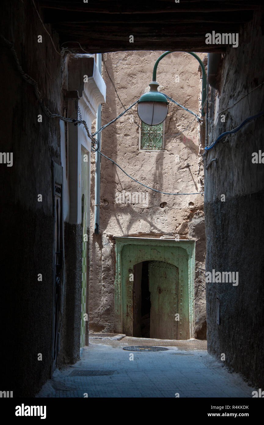 18-04-11.Marrakech, Morocco.  In the medina, a view down a lamp lit alley, to an ancient door / entrance to a house. Photo © Simon Grosset - Stock Image