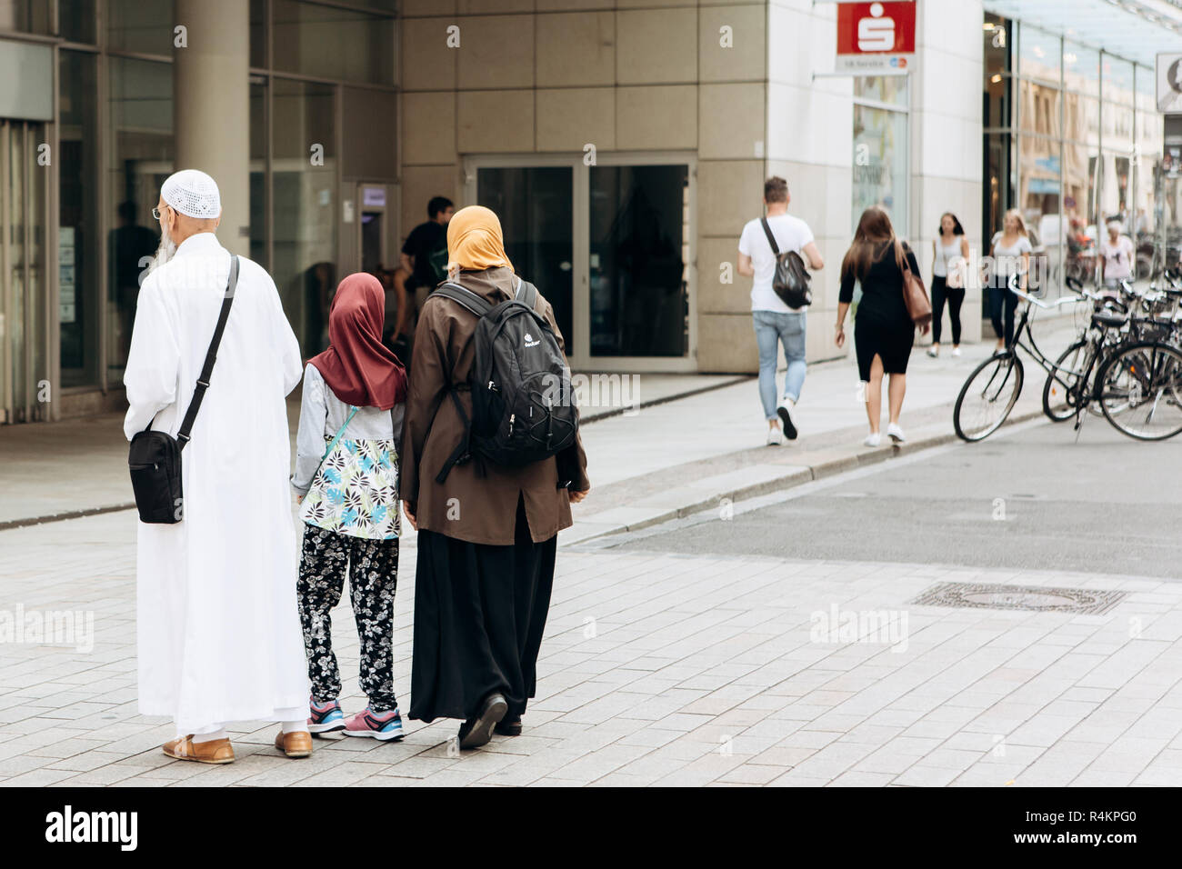 Germany, Leipzig, September 6, 2018: Friendly Arab family of tourists or migrants walking along the street of Leipzig in Germany on a summer sunny day. - Stock Image