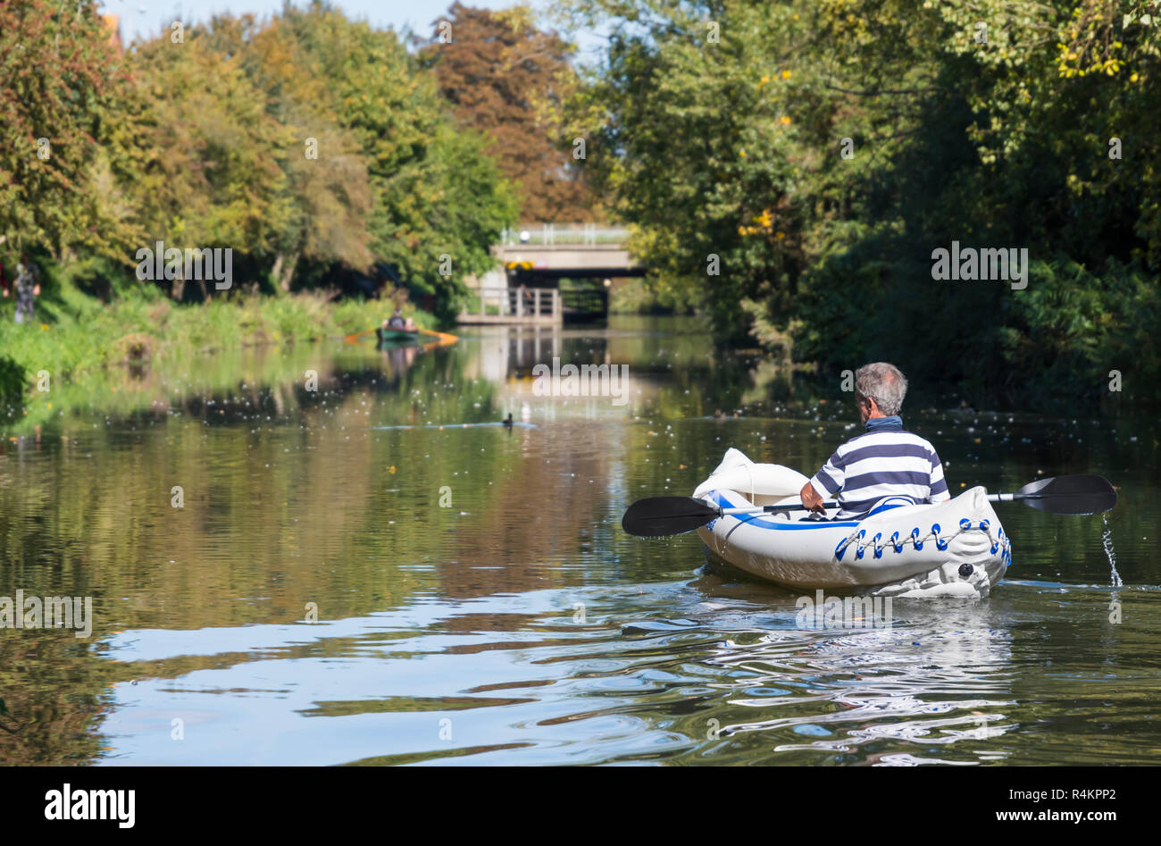 Man in a Sea Eagle SE-370 inflatable kayak on the Chichester Canal in Autumn in West Sussex, England, UK. Man kayaking. - Stock Image