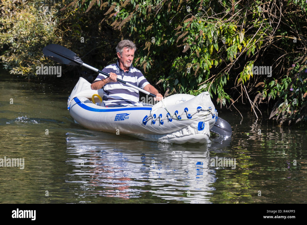 Middle aged man paddling with a double bladed paddle in a Sea Eagle SE-370 inflatable kayak, on a canal in the UK. - Stock Image