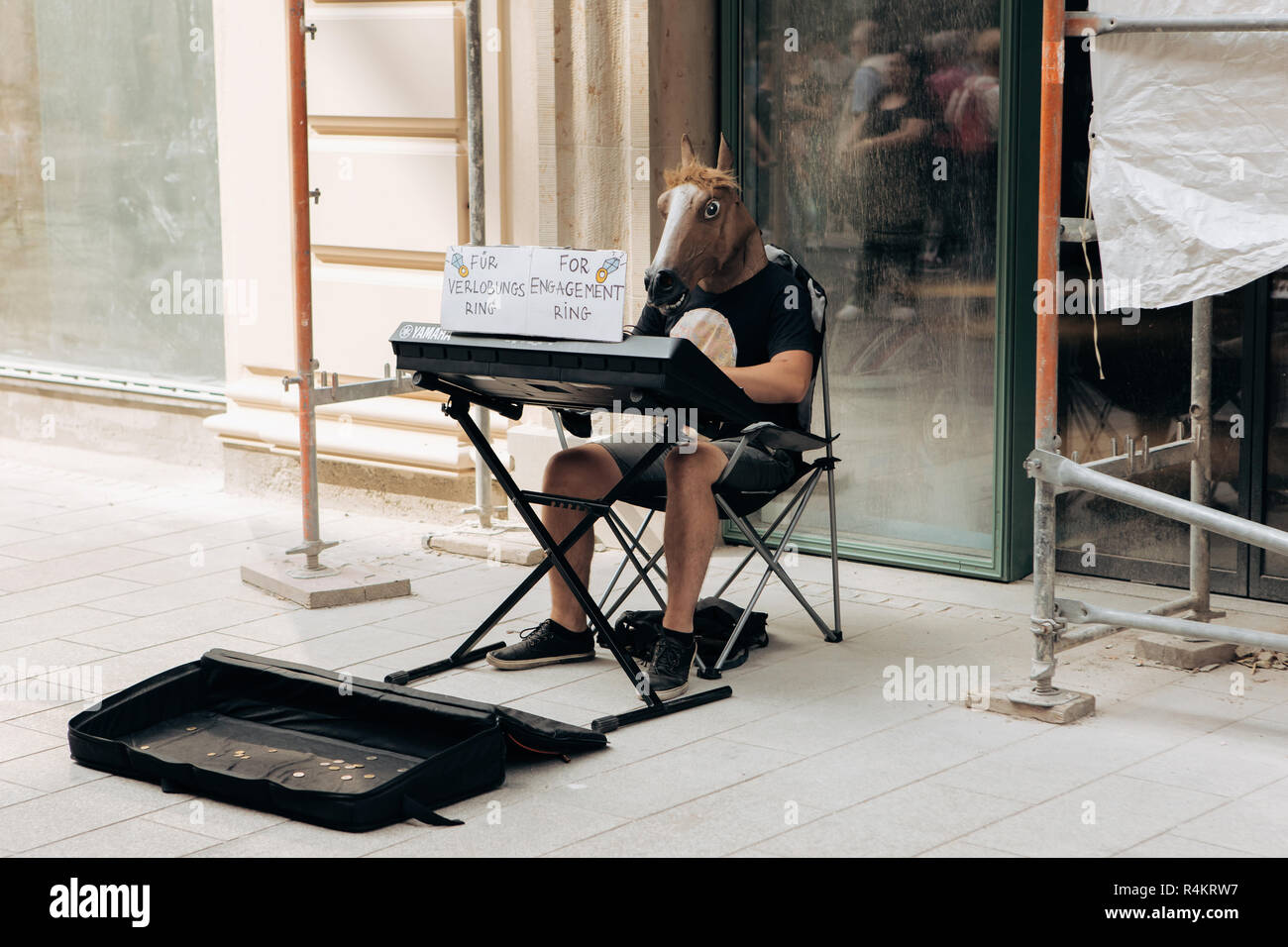 Germany, Leipzig, September 6, 2018: A creative musician with a horse's head plays on a synthesizer on Leipzig street to collect money for an engagement ring. - Stock Image