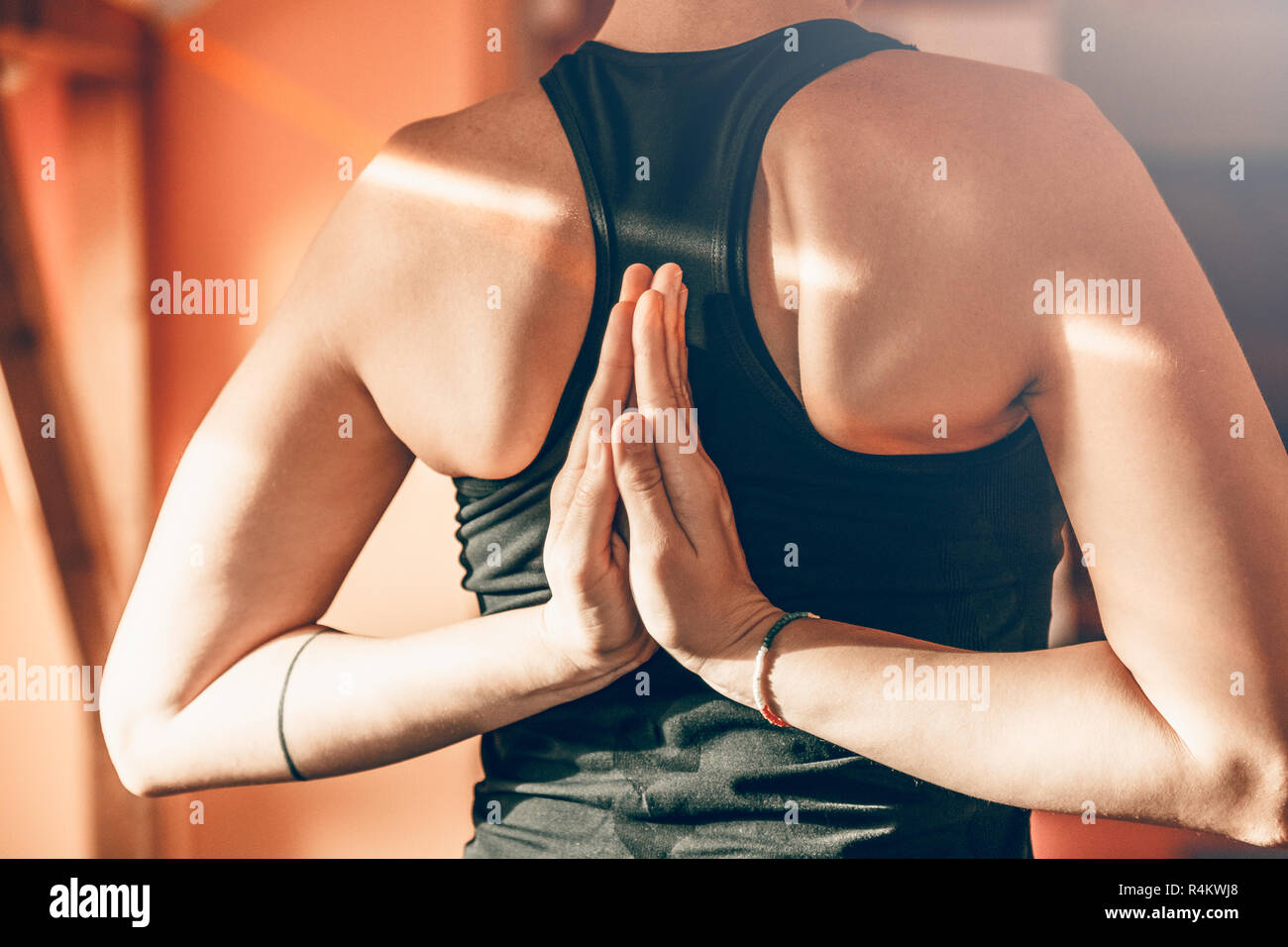 Rear view of woman doing yoga reverse prayer position. - Stock Image