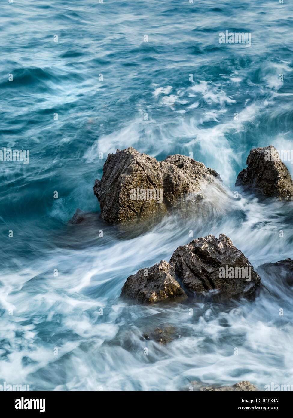 Sea turbulent waves atop rough rocky coastline - Stock Image