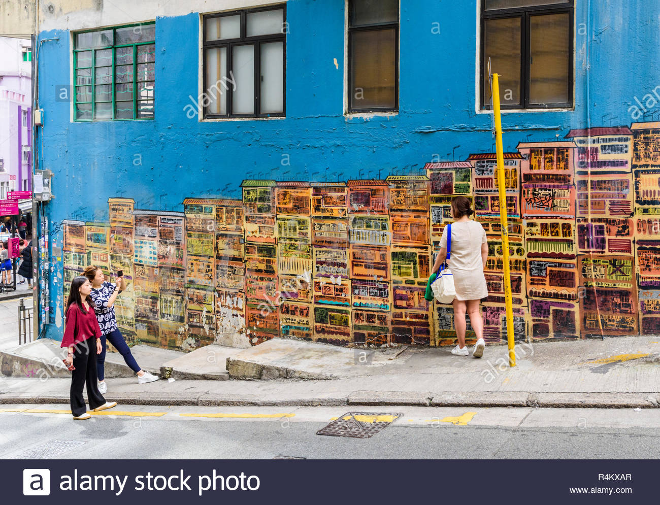 People taking photos next to the public street art murals of old townhouses along Graham St, Central, Hong Kong - Stock Image