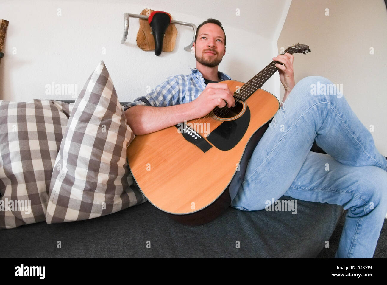 Young male sitting on a sofa playing his acoustic guitar Stock Photo