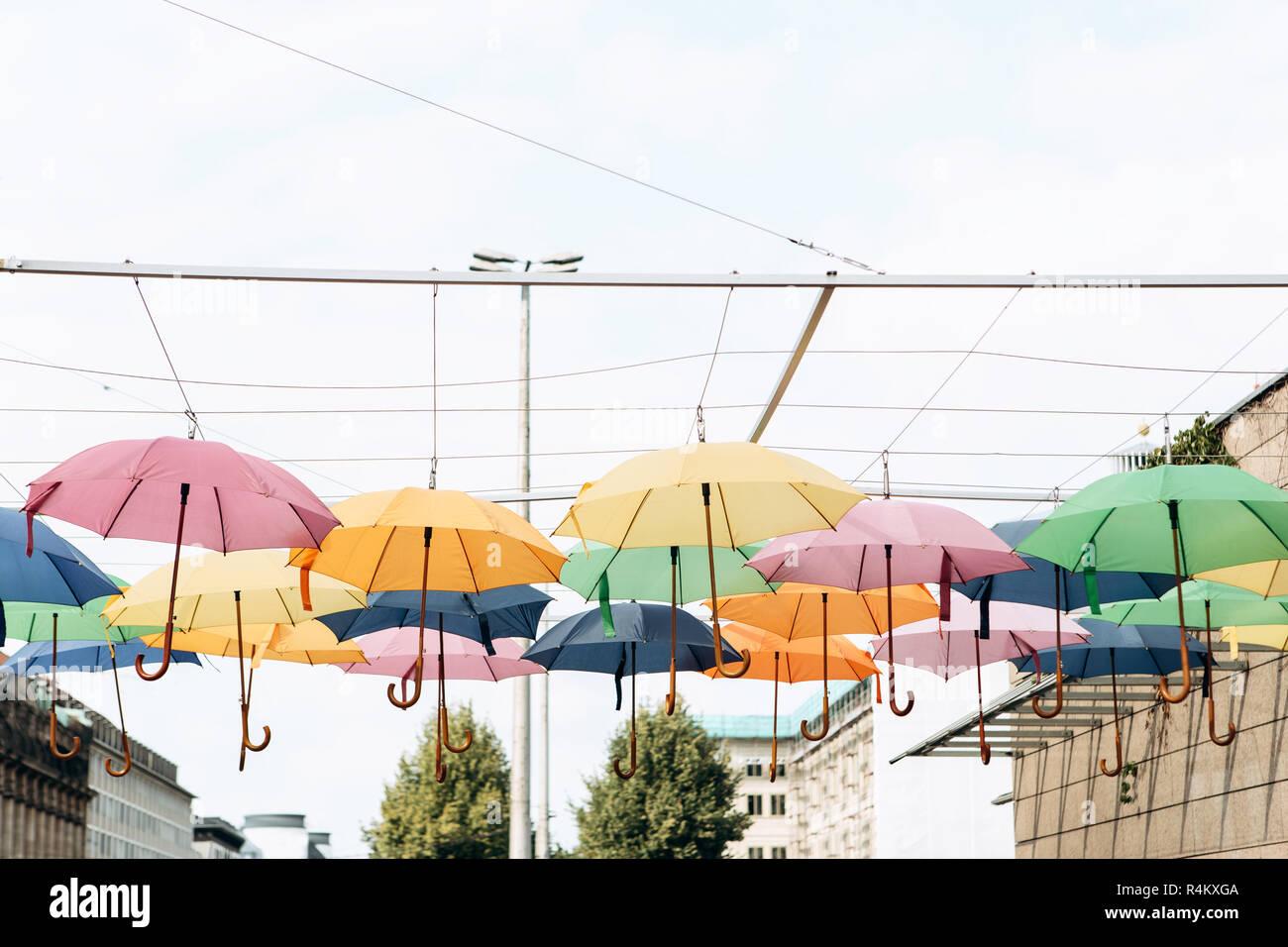 Lots of colorful umbrellas hang overhead. Creative idea. - Stock Image