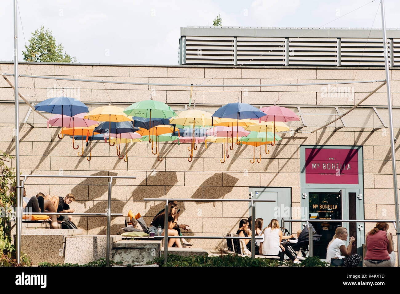 Germany, Leipzig, September 6, 2018: Creative cafe in Leipzig. Lots of colorful umbrellas hang overhead. People relax, chat and eat - Stock Image