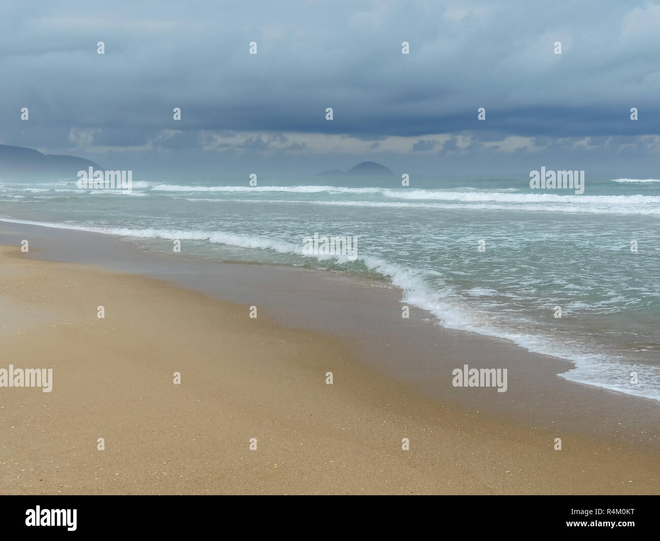 Eye level view of a beach with some low waves in the Florianópolis island - Stock Image