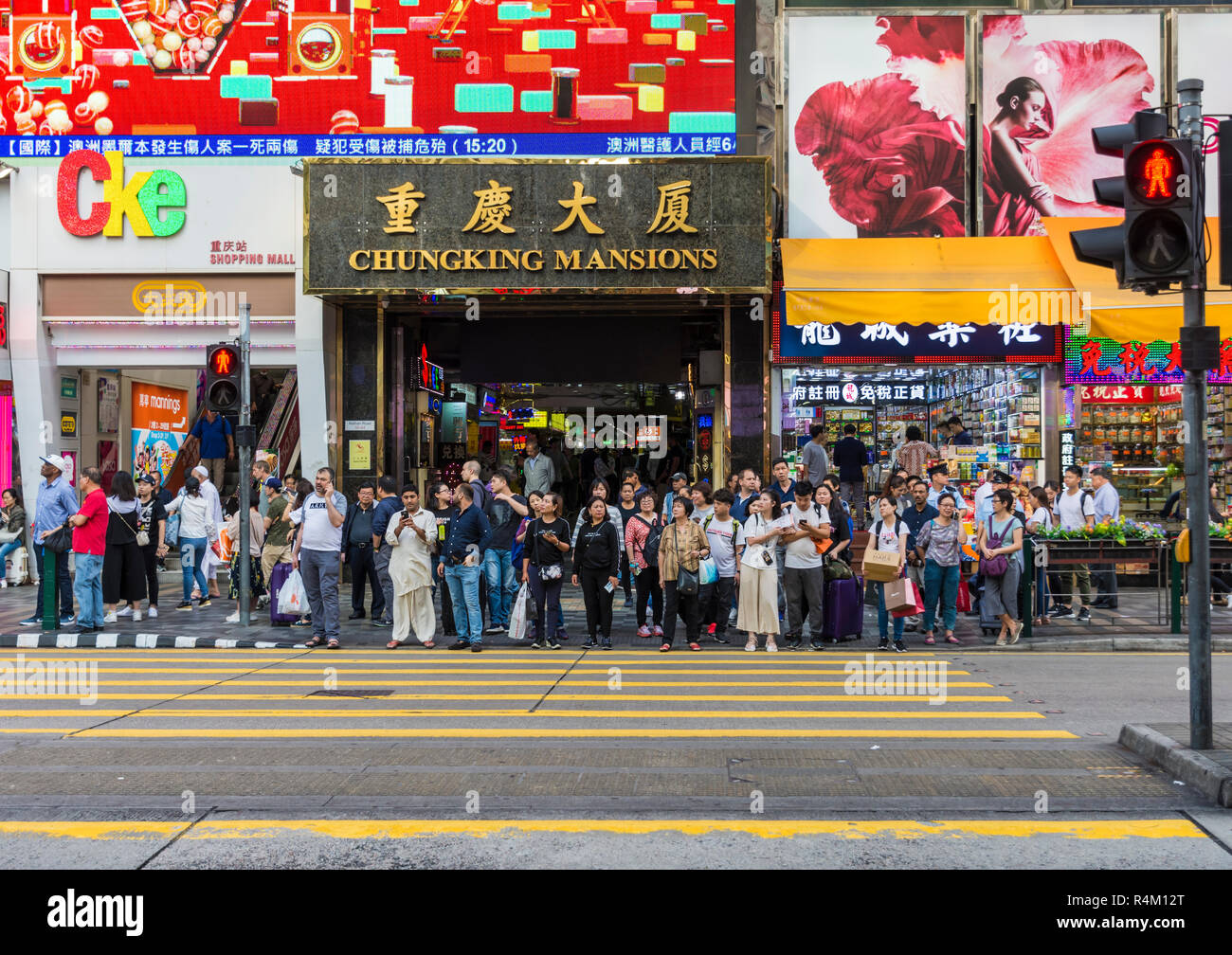 People waiting at the crosswalk outside Chungking Mansions, Nathan Road, Tsim Sha Tsui, Kowloon, Hong Kong - Stock Image