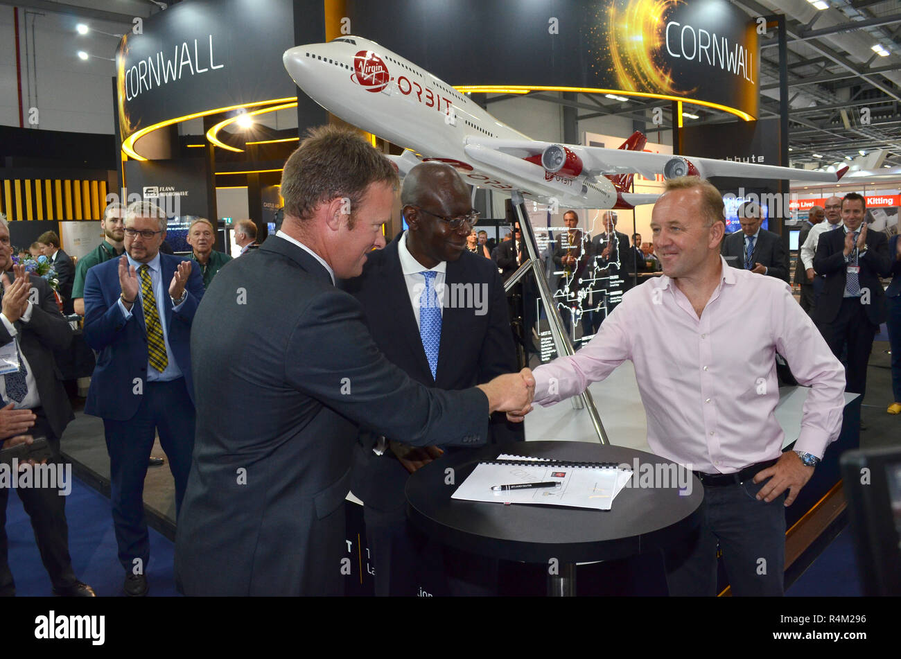 Leader of Cornwall Council Adam Paynter (left) shakes hands with Patrick McCall, chairman of Virgin Orbit, with UK Science Minister Sam Gyimah Stock Photo