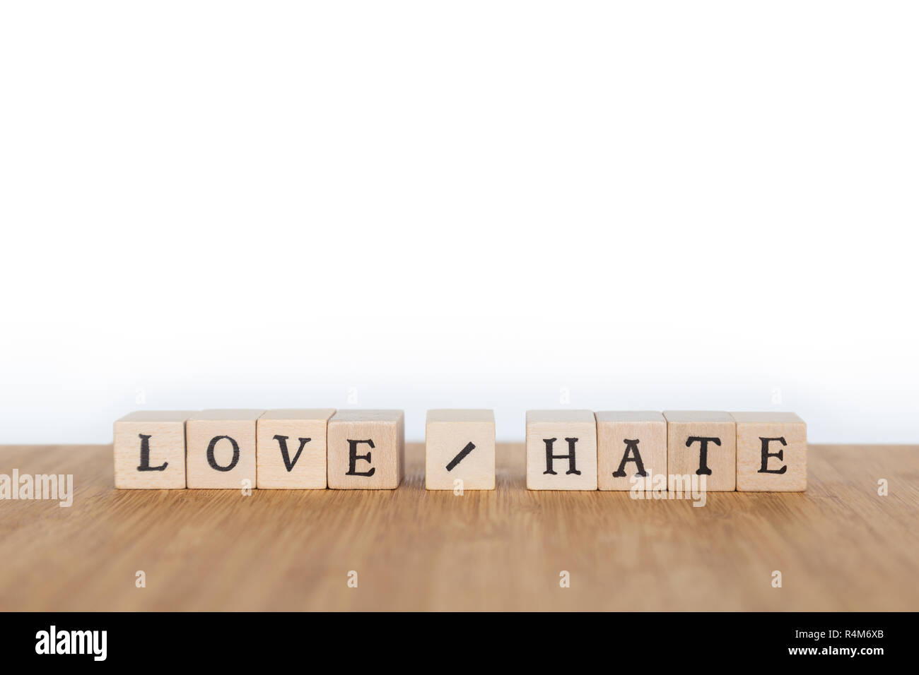 Focus on the words 'Love / Hate' made of wooden block dice with letters on a wooden table. Shallow depth of field. Copy space. - Stock Image