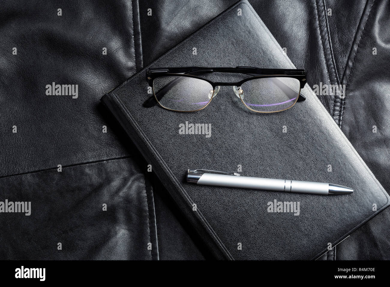 Notebook, glasses and pix over black leather background. Business minimalist lifestile presentation background. - Stock Image