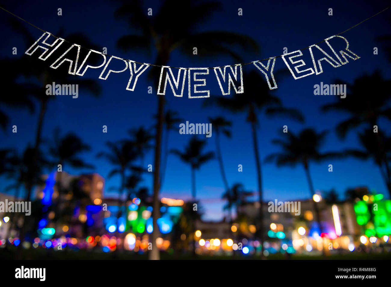 happy new year message hanging in glittery party bunting above tropical palm trees of the glowing neon lights of the skyline of miami beach florida