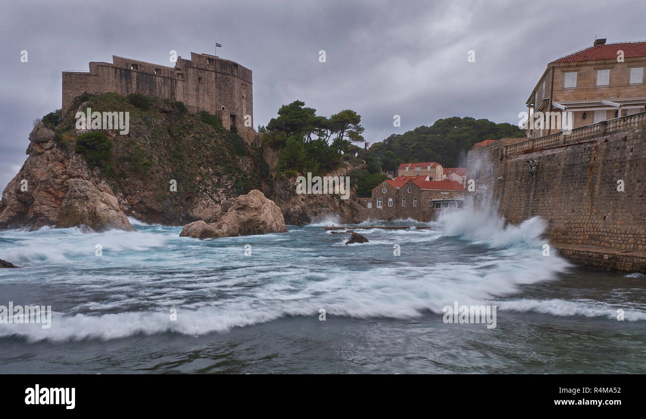 Fort Lovrijenac in Dubrovnic as seen from the beach on a stormy day, with crashing waves and dark clouds. Stock Photo