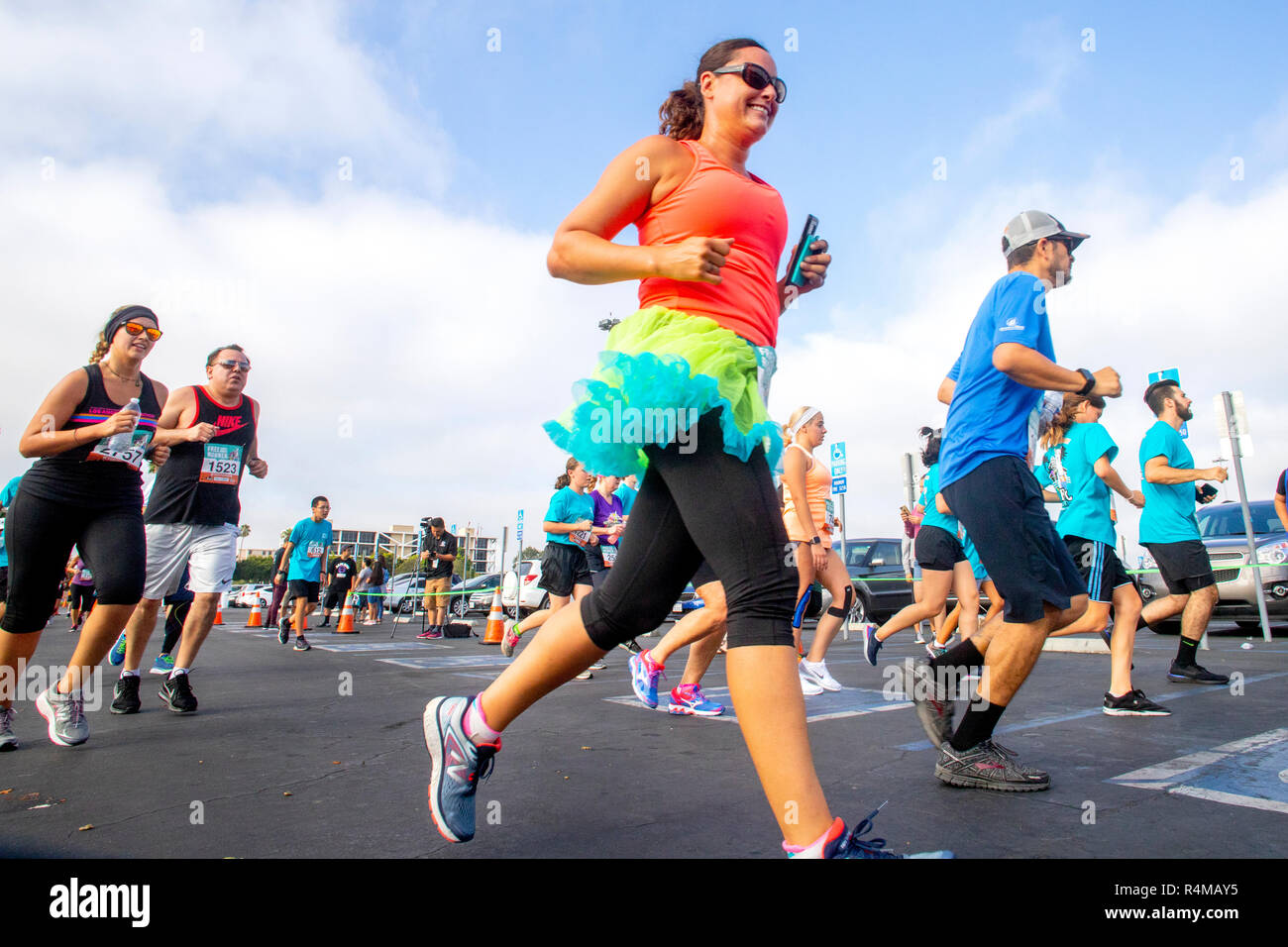 Participants in a 5K 'Fun Run' race through a fairground parking lot in Costa Mesa, CA. - Stock Photo