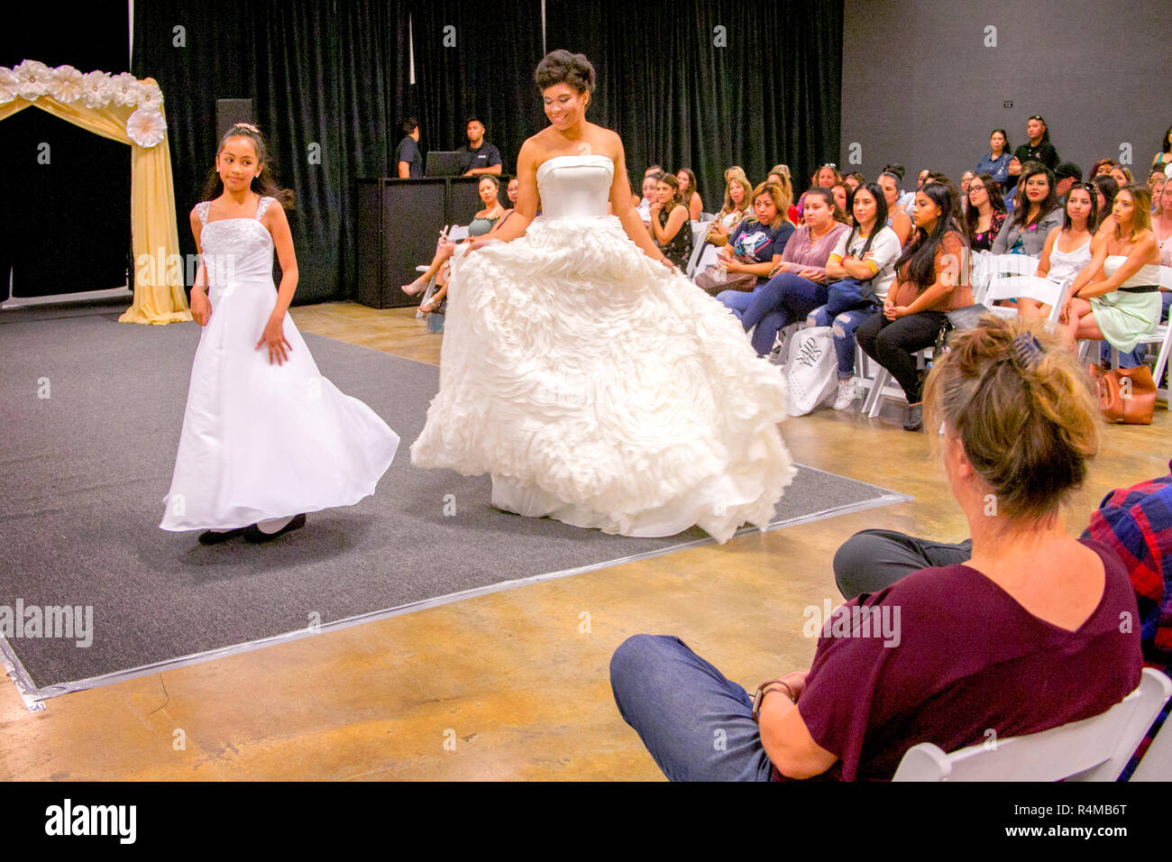 fbfd0b72a A Hispanic mother and daughter model bridal and bride's maid dresses at a  bridal fair fashion