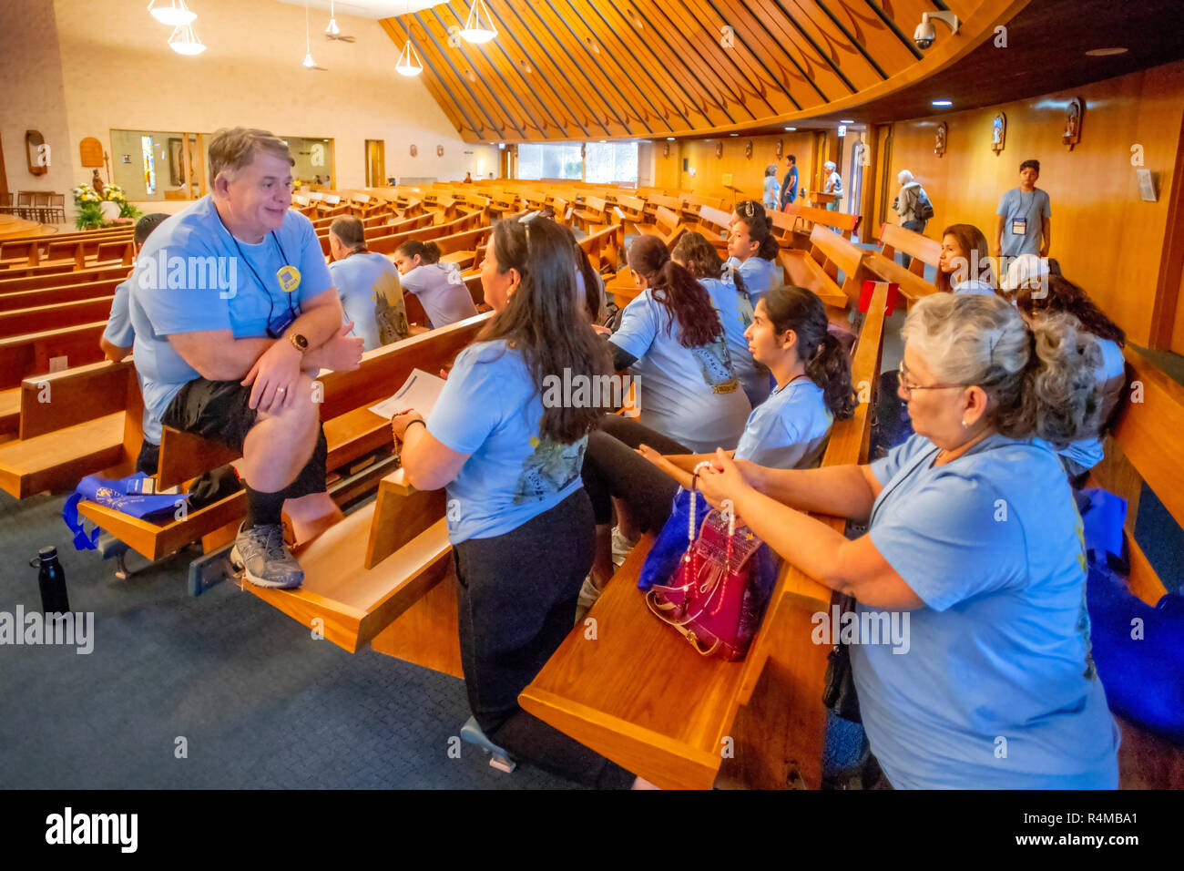 A deacon meets with parishioners after a congregational pilgrimage at a Lake Forest, CA, Catholic church. - Stock Image