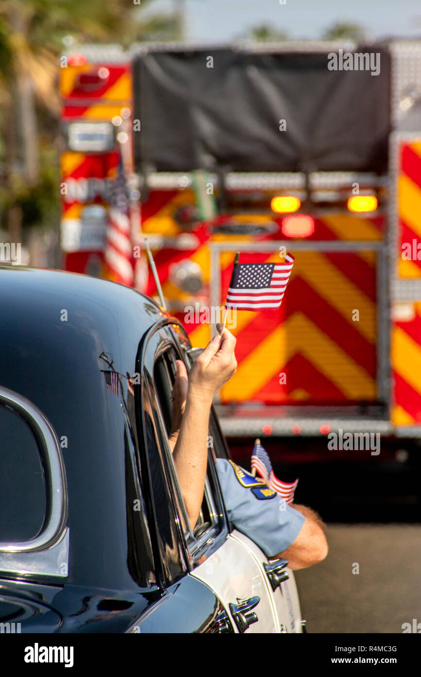 An American flag flutters from the window of an antique 1951 police car as it follows a fire engine in a Fourth of July parade in Newport Beach, CA. - Stock Image