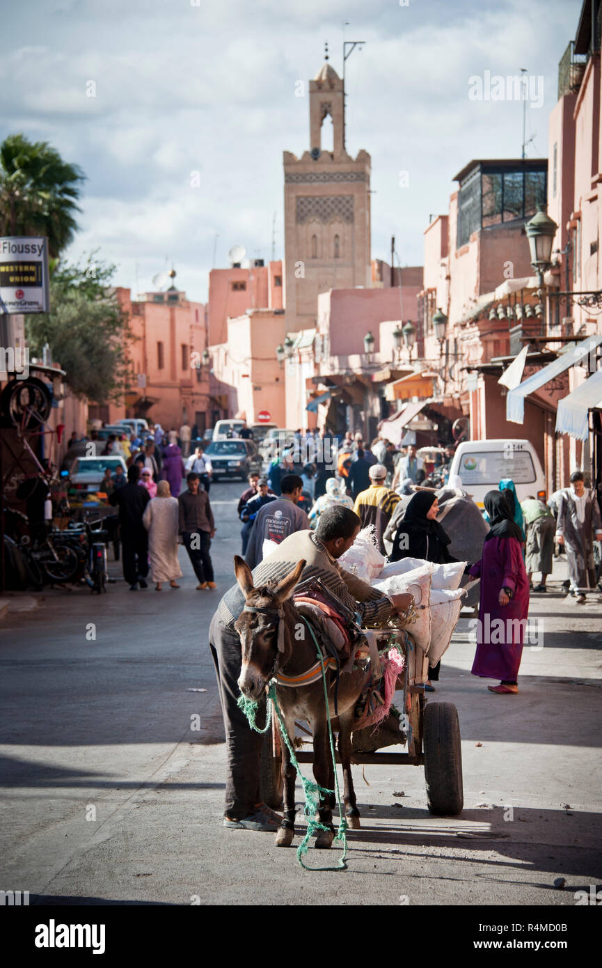 18-04-11. Marrakech, Morocco.  Pedestrians, cars and donkeys share the road in the medina, with a minaret of a mosque in the background. Photo © Simon - Stock Image