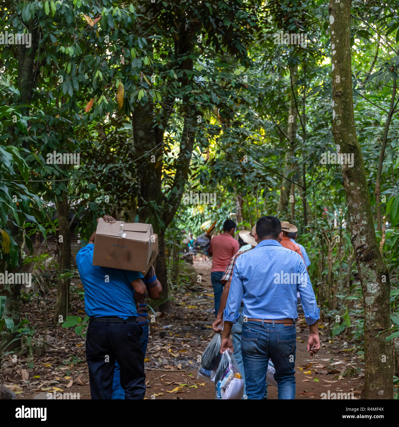 christian missionaries carrying supplies and food to remote village in Guatemalan jungle - Stock Image