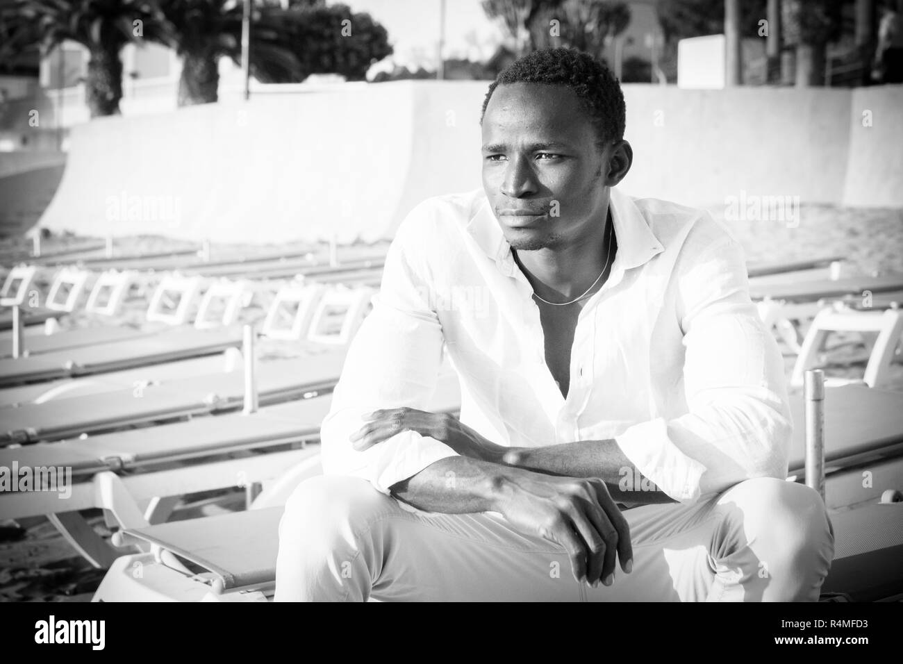 fashion black and white style pictures portrait african beautiful model man sitting at the beach looking in front of him - beauty concept for attracti - Stock Image