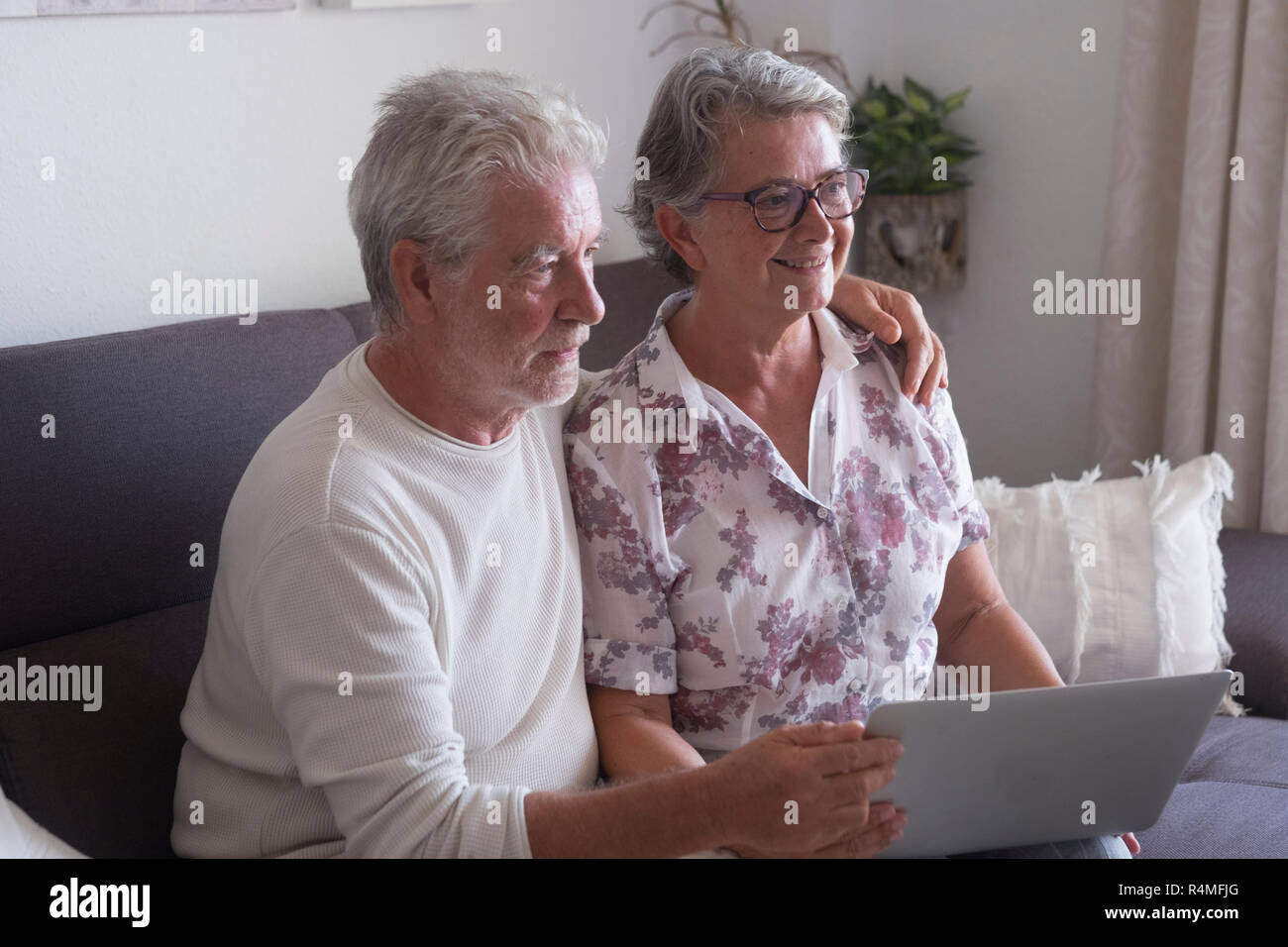 Senior couple at home websurfing on laptop computer - woman smiling and man serious both looking for something on internet and use a notebook sit down - Stock Image
