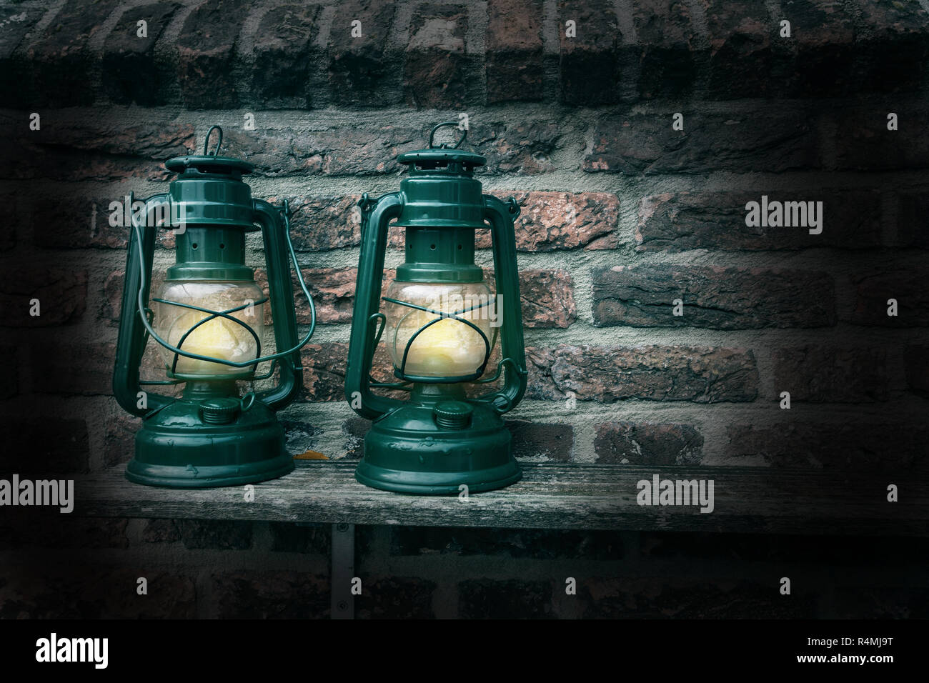 Old antique oil Lamp at Night on a Wooden Surface - Stock Image