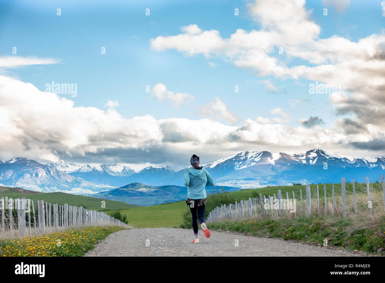 Woman running on a dirt road with beautiful mountains in the background near Coyhaique, Chile in the Aysen Region near Patagonia. - Stock Image