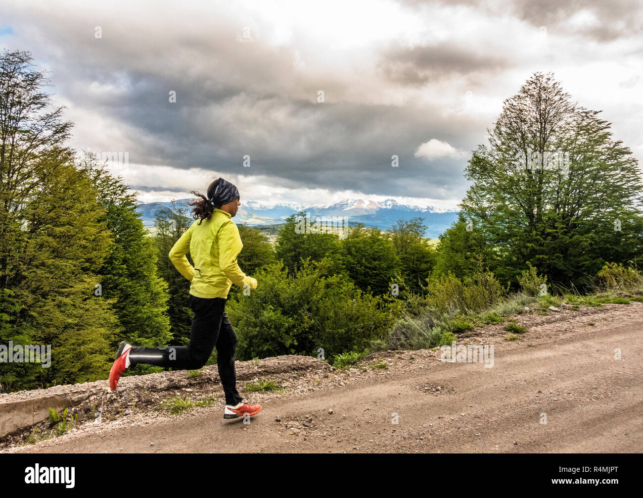 Athlete running on a dirt road near Coyhaique, Chile in the Aysen Region of Patagonia. - Stock Image