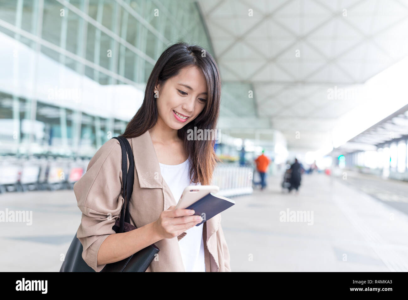 Woman looking at cellphone in Hong Kong airport - Stock Image