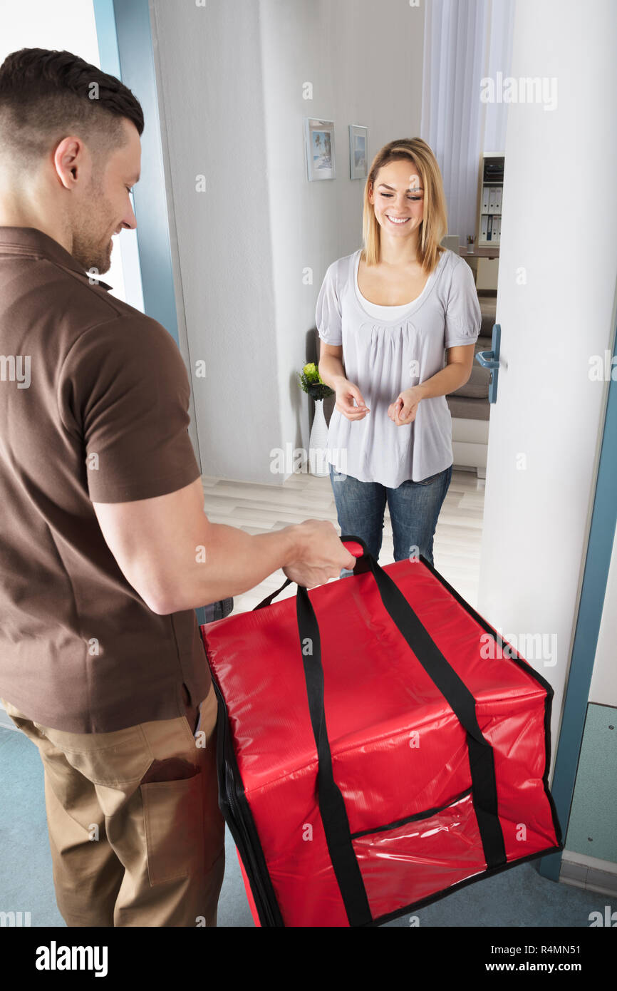 Delivery Man Giving Bag To Woman - Stock Image